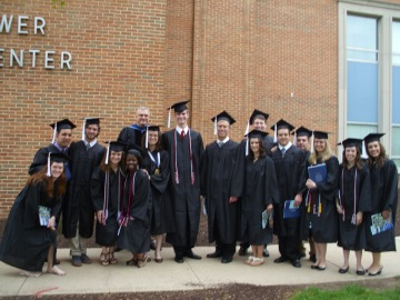 History graduates hold up the procession to get a group picture